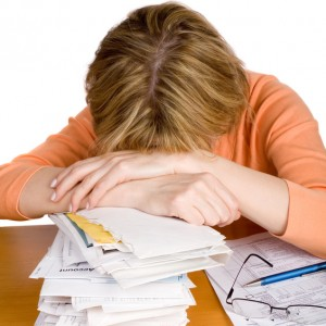 A woman exhausted with tax return form. a stack of bills by her side. Extracted. White background.